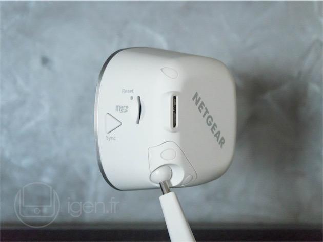 La tranche (avec le bouton de synchronisation et le logement micro-SD) et le dos (avec le connecteur d'alimentation micro-USB 3.0) de la caméra. Remarquez la fixation/articulation par rotule…et le logo Netgear relégué là où on ne le verra pas.